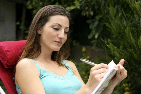 zena zapisuje svoja zapazanja u dnevnik