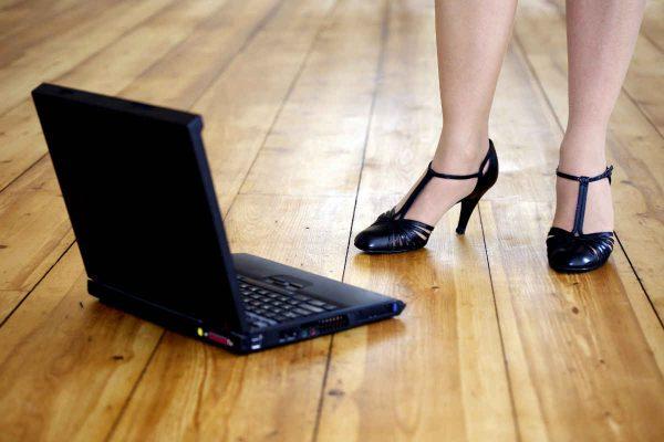 zena u stiklama drzi laptop na podu