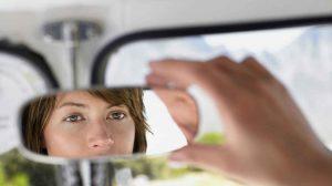 zena gleda svoju refleksiju u ogledalu u kolima