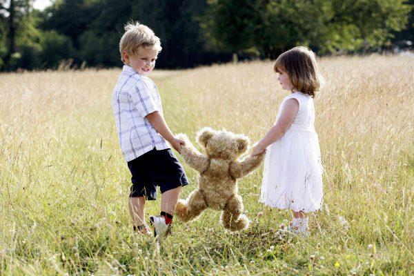 decak i devojcica se igraju sa plisanim medom