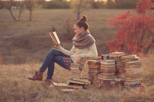 Devojka cita knjige na livadi